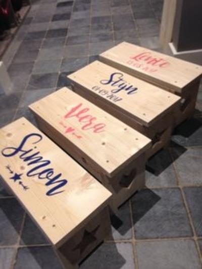 Steigerhouten bankje met beschilderde naam .